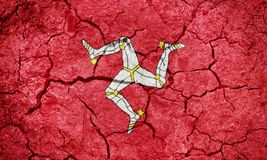 Isle of Man flag. On dry earth ground texture background stock photos