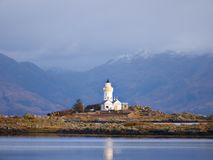 Isle Ornsay with white tower of Lighthouse; Isle of Skye; Scotland. Sunny winter day with snowy mountains stock images
