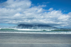 Isle of Rum with Crashing Wave. Isle of Rum, Scotland, with Crashing Wave, from Laig Bay on Eigg Royalty Free Stock Photo