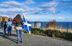Isle of Skye , Scotland - October 14 2018 : Tourists visiting the Kilt Rock waterfall by Staffin with a waving flag.  royalty free stock photos