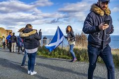 Isle of Skye , Scotland - October 14 2018 : Tourists visiting the Kilt Rock waterfall by Staffin with a waving flag.  stock image
