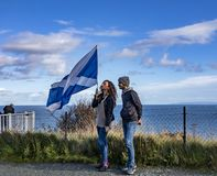 Isle of Skye , Scotland - October 14 2018 : Tourists visiting the Kilt Rock waterfall by Staffin with a waving flag.  stock photo