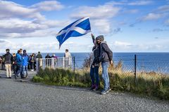 Isle of Skye , Scotland - October 14 2018 : Tourists visiting the Kilt Rock waterfall by Staffin with a waving flag.  stock photography