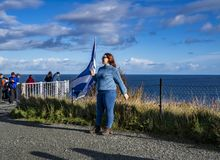 Isle of Skye , Scotland - October 14 2018 : Tourists visiting the Kilt Rock waterfall by Staffin with a waving flag.  stock photos