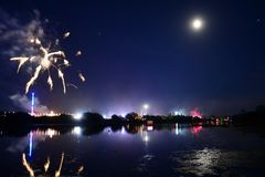 The Isle of Wight Festival Fireworks Finale. Fireworks, lights and a near full `strawberry` moon reflect off the River Medina on the last night of the 2018 Isle Stock Images