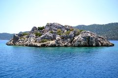 Islet in the Mediterranean sea. Small stone island in the Mediterranean sea and the mountains, against the sky Royalty Free Stock Photography