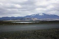 Isländskt berglandskap med vägen Arkivfoton