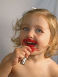 Isn't she lovely?. Little girl trying on red lipstick royalty free stock photography
