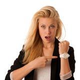 年轻白肤金发的妇女看看她的手表,当她是晚iso 库存图片