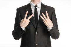 商人和姿态题目:一套黑衣服的一个人与显示与他的右手两只或三只左手标志iso的领带一个标志 库存照片