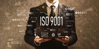 ISO 9001 with businessman holding a tablet computer. On a dark vintage background royalty free stock images