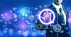 ISO 9001 with businessman. On blurred blue light background stock photography