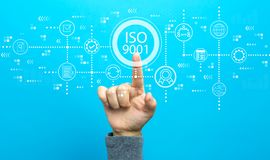 ISO 9001 with hand. On a blue background stock photo