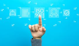 ISO 9001 with hand. On a blue background stock photography