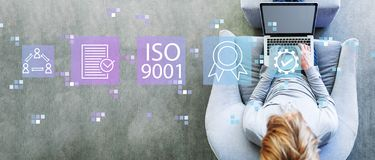 ISO 9001 with man using a laptop. In a modern gray chair stock image