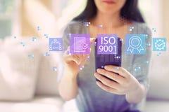 ISO 9001 met vrouw die een smartphone gebruiken stock foto