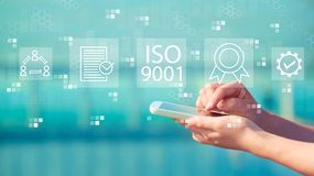 ISO 9001 with smartphone. ISO 9001 with person holding a white smartphone royalty free stock photography