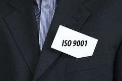 Iso 9001 text concept. Iso 9001 text note concept over businessman background Royalty Free Stock Photography