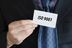 Iso 9001 text concept. Iso 9001 text note concept over businessman background Royalty Free Stock Images