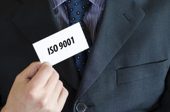 Iso 9001 text concept. Iso 9001 text note concept over businessman background Royalty Free Stock Photo