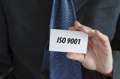 Iso 9001 text concept. Iso 9001 text note concept over businessman background Stock Images