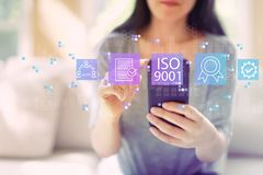 ISO 9001 with woman using a smartphone. ISO 9001 with woman using her smartphone in a living room stock photo