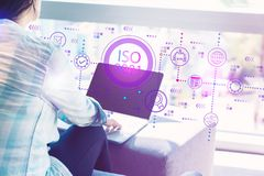 ISO 9001 with woman using laptop. ISO 9001 with woman using her laptop in her home office stock image