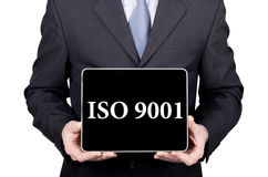 ISO 9001 written on virtual screen. technology, internet and networking concept. man in a business suit and tie holds a Royalty Free Stock Image
