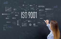 ISO 9001 with young woman. Writing on a blackboard royalty free stock images