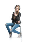Isolée sur la fille blanche est musique l'écoute dans des écouteurs de câble Photographie stock