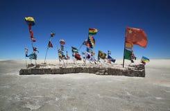 Isola con le bandiere in Salar de Uyuni, Bolivia Immagine Stock Libera da Diritti