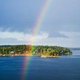 Isola con lo stabilimento ed arcobaleno in cielo blu Immagini Stock Libere da Diritti
