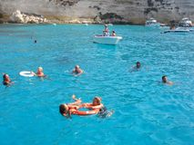 Isola dei Conigli beach in Lampedusa. Lampedusa, Italy - September 24, 2002 : Tourists swimming in Rabbits beach royalty free stock photos