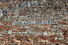 Isola Del Deserto - Venice. The city name of Isola Del Deserto built into an old ancient wall Royalty Free Stock Image