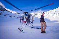 ISOLA DEL SUD, LA NUOVA ZELANDA 24 MAGGIO 2017: Chiuda su dell'elicottero e di aspettare pilota sopra la neve i cacciatori nel su Immagine Stock Libera da Diritti