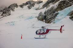 ISOLA DEL SUD, LA NUOVA ZELANDA 24 MAGGIO 2017: Chiuda su dell'elicottero rosso che aspetta sopra la neve i cacciatori in Westlan Immagini Stock Libere da Diritti