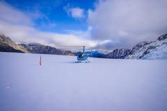 ISOLA DEL SUD, LA NUOVA ZELANDA 24 MAGGIO 2017: Elicottero e pilota che aspettano sopra la neve i cacciatori nel ` del sud s di W Immagine Stock
