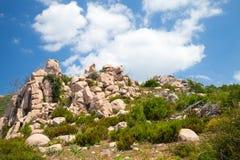 Isola di Corsica, montagne rocciose sotto il cielo nuvoloso Immagini Stock