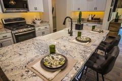 Isola di cucina con il ripiano del granito e le regolazioni di posto fotografie stock