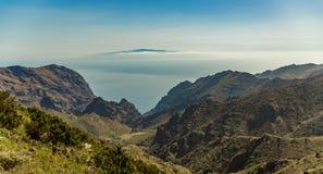 Isola di La Gomera, in ascesa sopra l'orizzonte, coperto parzialmente dalle nuvole Cielo blu luminoso Metri di vista dal 1900 di  immagini stock libere da diritti