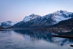 Isola di Lofoten alla notte, con i picchi nevosi nella parte posteriore e nel paesino di pescatori con le luci della città nella  immagini stock