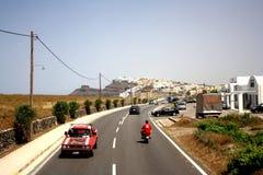 Isola di Santorini, Grecia - 5 maggio 2013: Una strada sull'isola con un'automobile rossa e un uomo sul motocycle immagini stock