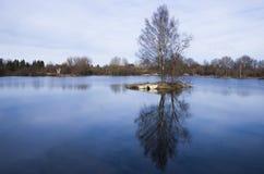 Isola in lago blu Immagine Stock