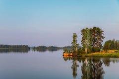 Isola luminosa su un lago con i pini alla luce di mattina fotografia stock libera da diritti
