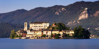 Isola San Giulio on Lake Orta, Italy. Blue water and blue sky divided by the island and the mountain in the background Stock Images
