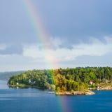 Isola verde con il villaggio ed arcobaleno in cielo blu Immagini Stock