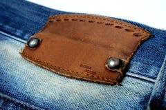 Isolado do couro da etiqueta da placa da sarja de Nimes das calças de brim do close up no branco foto de stock