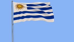 Isolate flag of Uruguay on a flagpole fluttering in the wind on a blue background  Stock Photography
