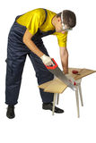 Isolate  man in the yellow shirt in overalls sawing board Royalty Free Stock Images