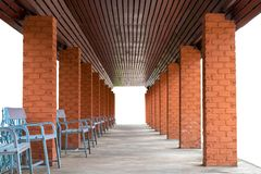 Square poles, brick walls and many benches. Isolate rows of pillar bricks with benches on concrete floors, which are used as entrances under brown wood ceilings stock images